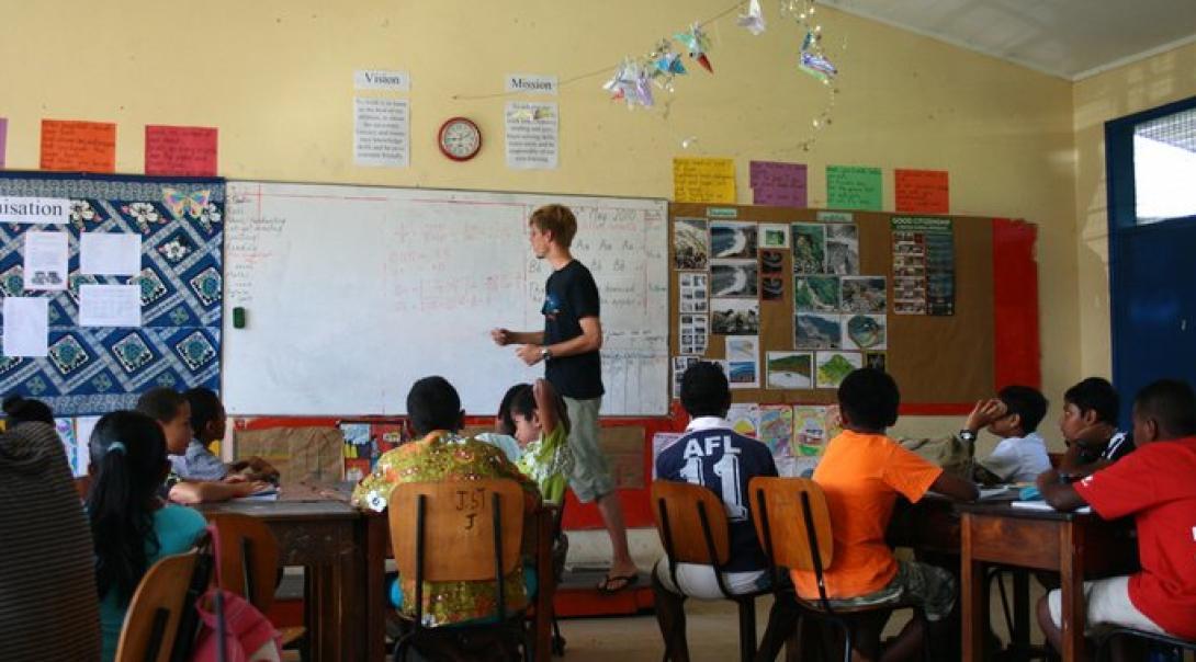 Un voluntario enseñándole matemáticas a niños locales durante su voluntariado de Educación en Fiyi.